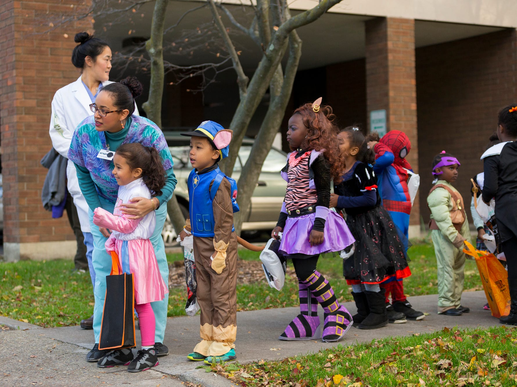 2015: Charlene Santos, who works in the kindergarten/first grade program at the Greater Ithaca Activities Center talks with five-year-old Janelle Lucena as they wait to lead the annual parade from McGraw House to The Commons for trick or treating Friday.