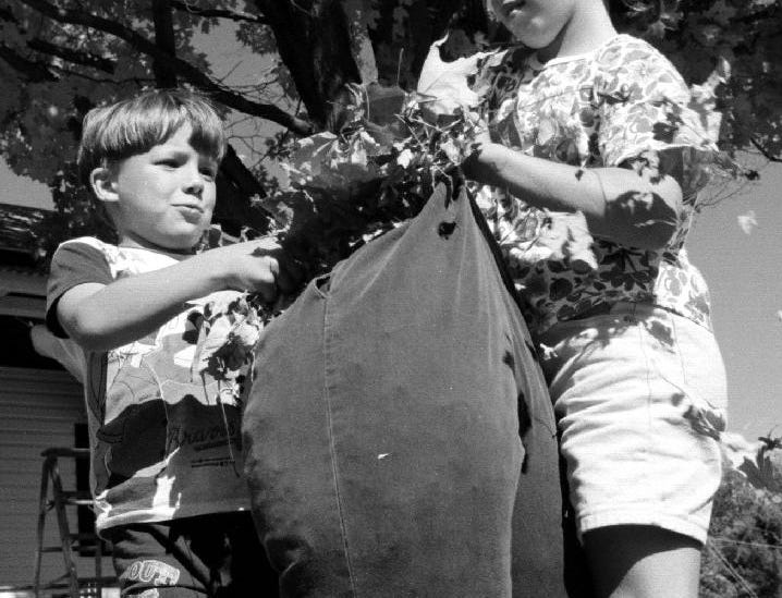 1997: Billy Dodd, 5, and his cousin, Jessica Gnall, 8, stuff a old pair of pants with leaves while building a scarecrow for a Halloween display at the Gnall's Town of Windsor home.
