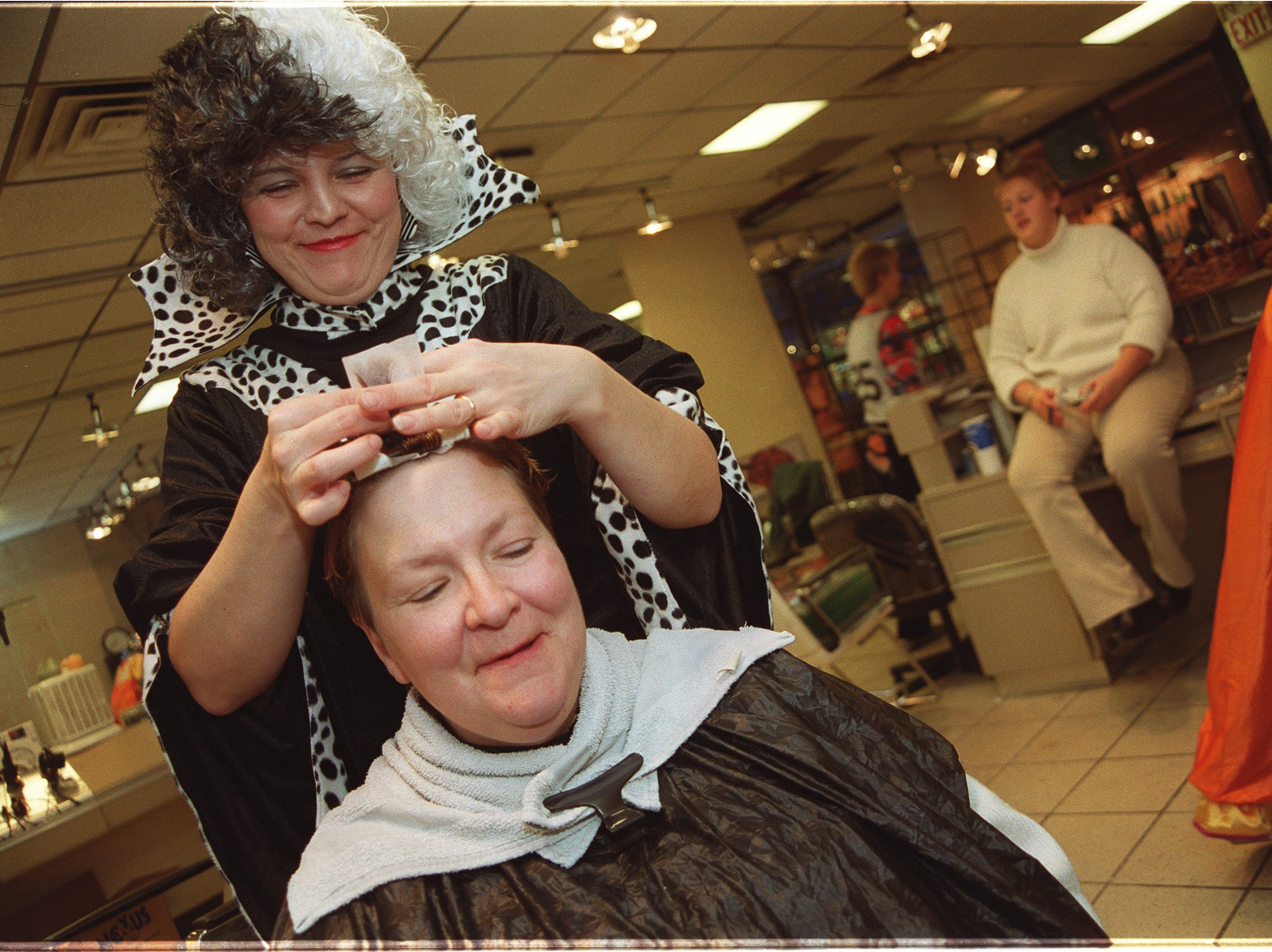 1999: `I love Halloween. It's my favorite holiday,' says Johanna Aasen, standing above, dressed at Cruella DeVill from Walt Disney's `101 Dalmatians.' Aasen gives Karen King, seated, a perm at the Regis Salon, a hair salon in the Pyramid Mall in Lansing. Aasen said she would wear her costume while taking her two children trick-or-treating.