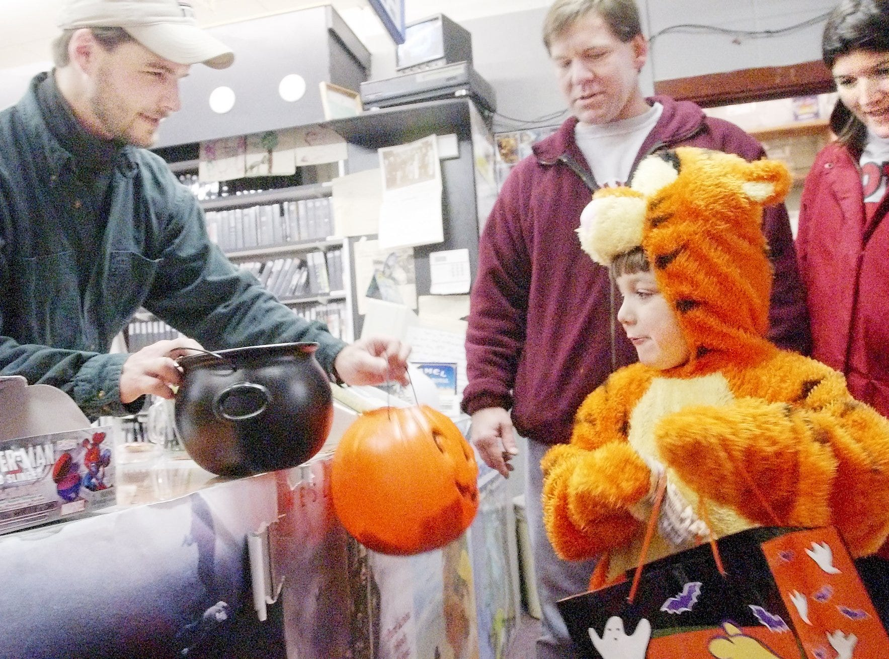 Jon Shufelt, left, owner of Groton's Village Video & DVD offers malted milk balls Thursday to Luke Lauchle, 5, who dressed up as Tigger for the Village of Groton trick-or-treat offered for Halloween by the downtown stores. Lauchle's parents, Lance and Terri look on.