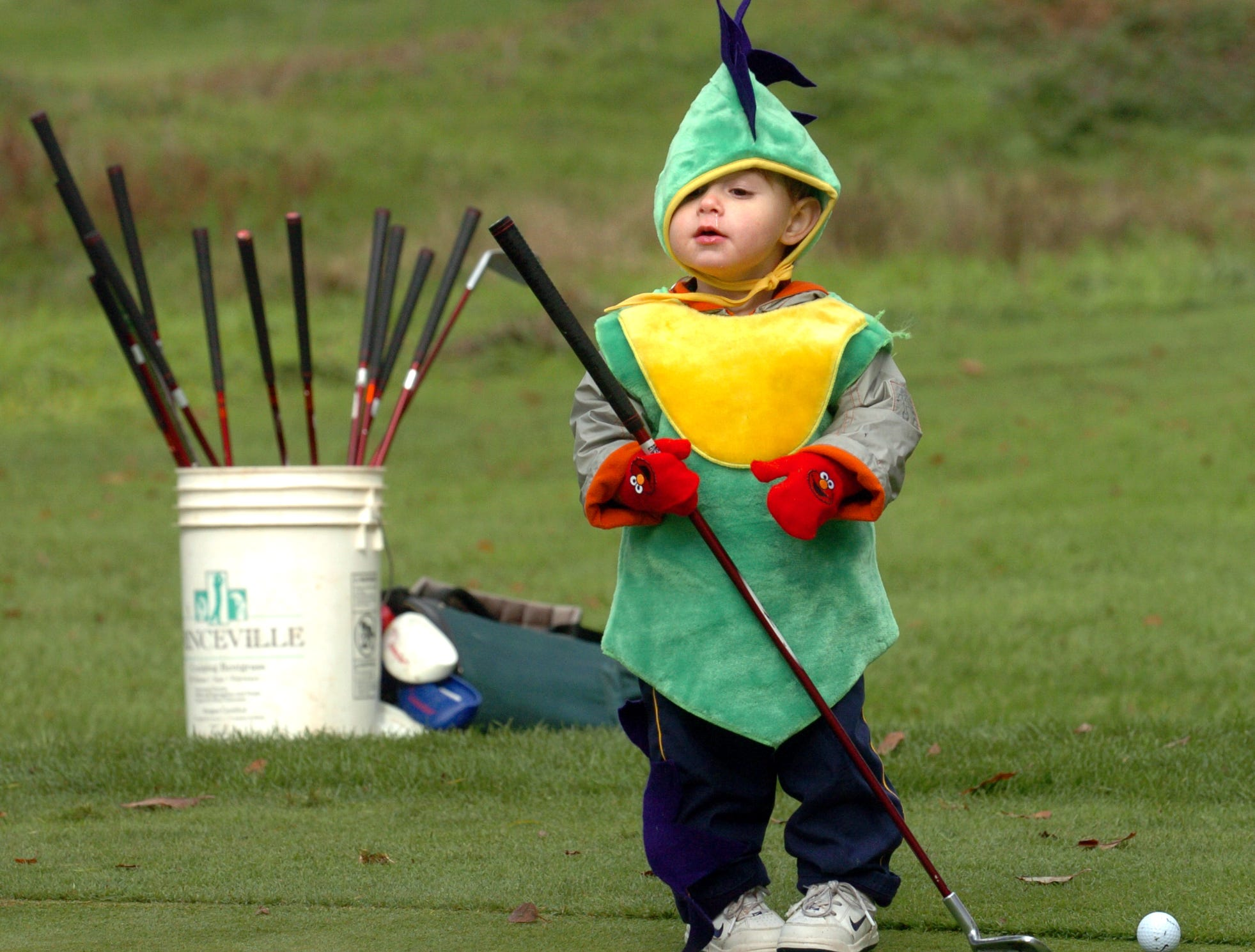 2005: 18-month-old Luca Richmond of the Town of Maine sports a dragon costume as he works on his golf skills during The First Tee of Hiawatha Landing's Halloween party Saturday morning.