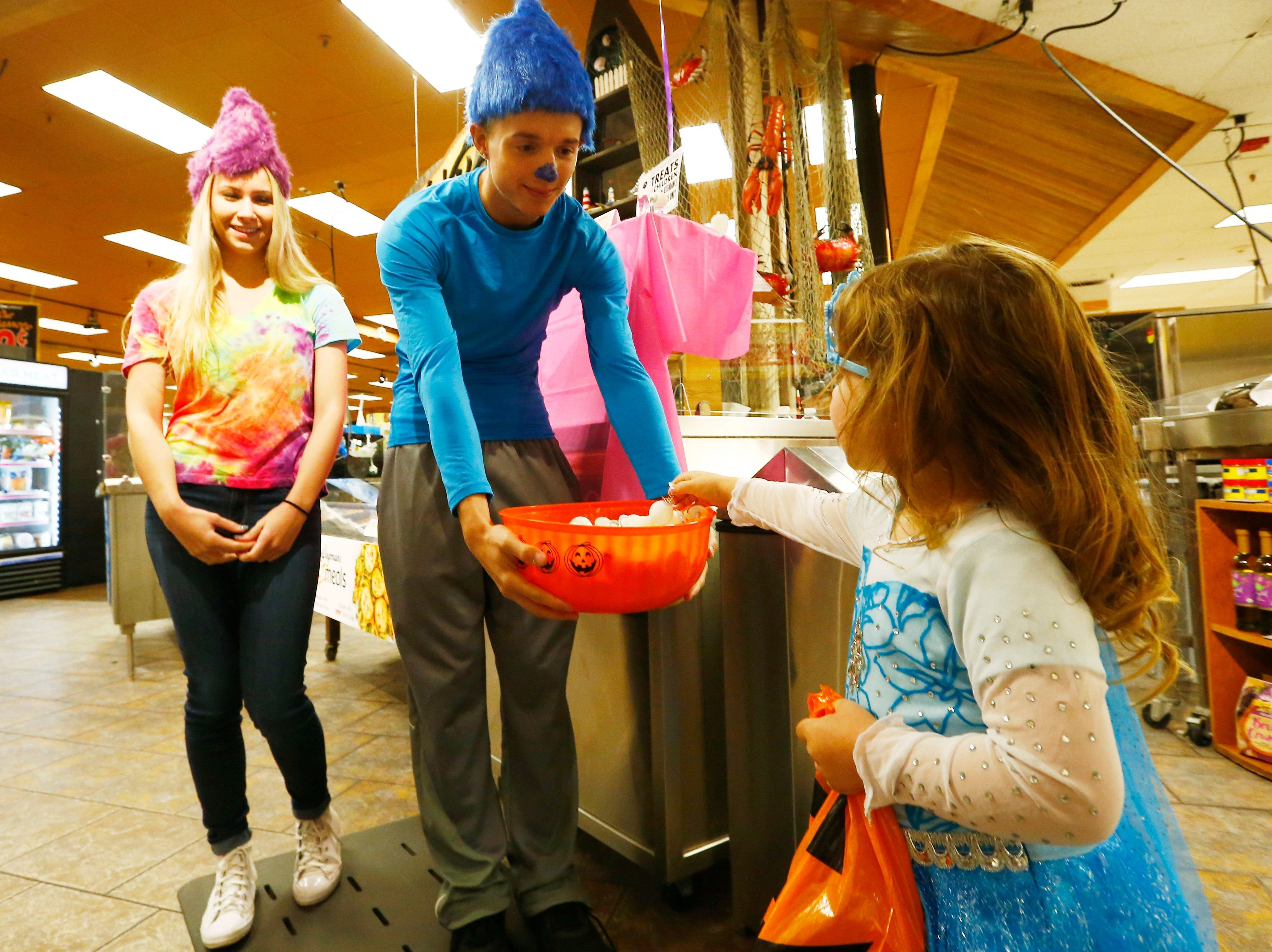 2017: Arianna Arraign of Windsor picks a treat from, from left, Morgan Kittle an Thomas Corey during Wegmans' Halloween Parade in Johnson City on Tuesday October 24, 2017.