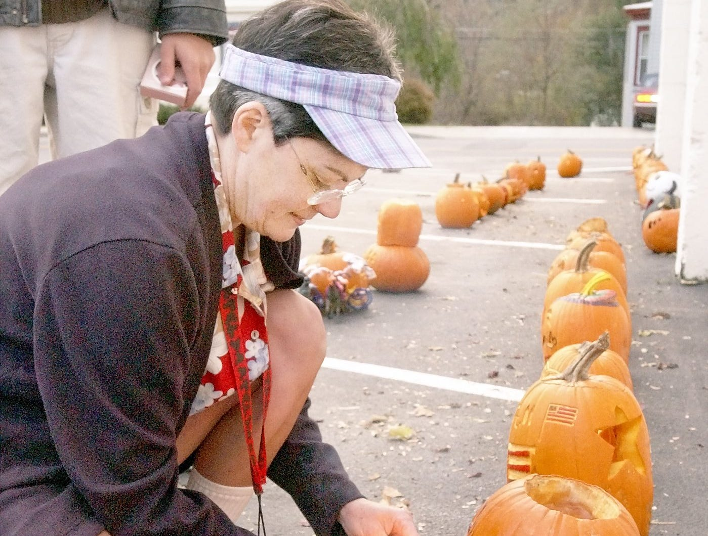 2002: Christy Walpole of Walpole's Liquor Store in Groton lights candles Thursday night to put inside the pumpkins entered in the annual Halloween Pumpkin Carving/Decorating Contest. Pumpkin decorations included a horse-drawn pumpkin carriage and a carving featuring Swiss cheese and a rat.