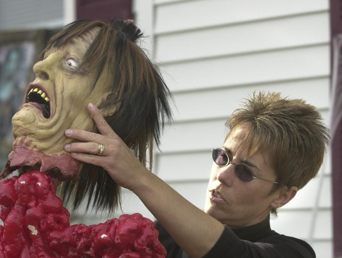 2004: Cheryl Racine mounts Halloween ghoul outside her Laurel Avenue house in Binghamton on Friday as she and Pam Stewart prepared their annual haunted house for Sunday.
