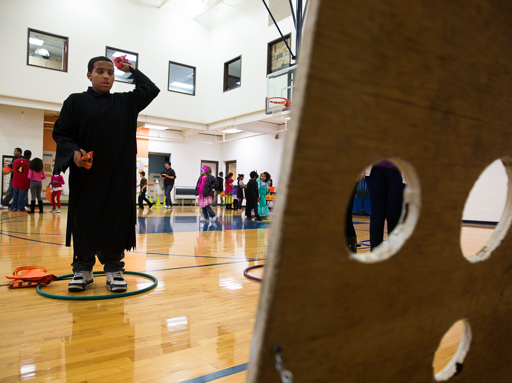 2013: Anthony Clinton Jr., age 12 of Binghamton, plays a bean bag toss game to earn tickets for prizes.  The Boys and Girls Club hosts a night of Halloween activities for children, including games, candy, food and a haunted house.