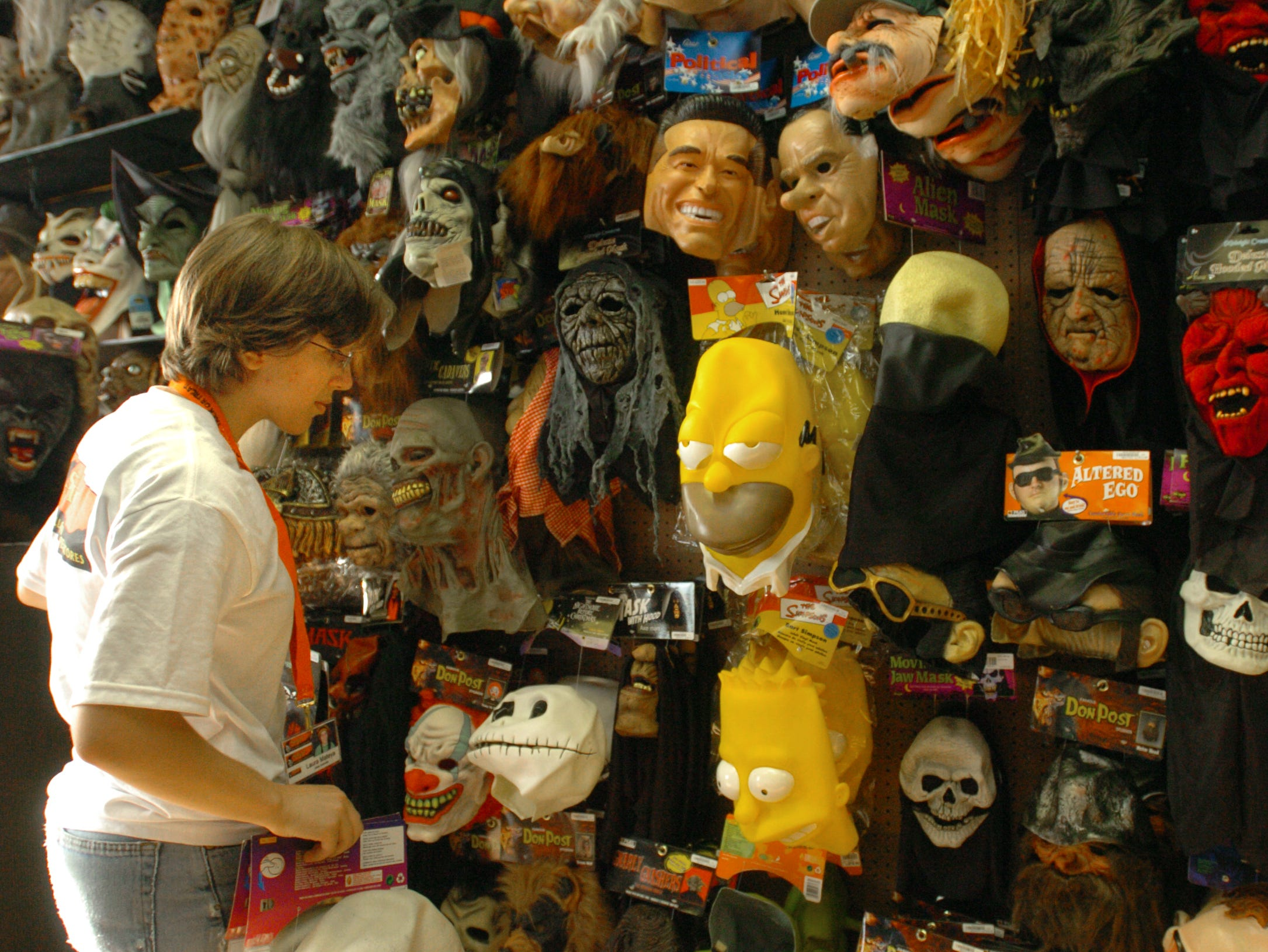 2005: Laura Mateya, 17, of Binghamton organizes masks among hundreds displayed on the wall at Spirit Halloween Superstore in Johnson City Monday afternoon. The business is new to the Southern Tier and is located on Reynolds Road across from the Oakdale Mall.