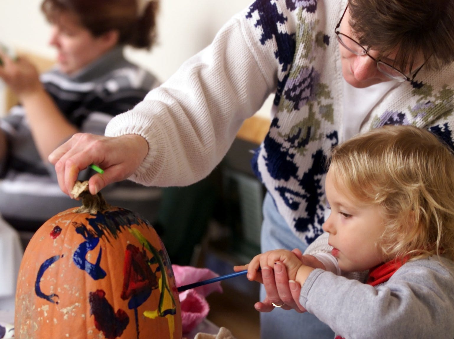 2002: Samantha Felko, 3, of Elmira paints a pumpkin with her grandmother Robin Van Atta also of Elmira at Tanglewood Nature Center's Haunted Happenings Halloween event Saturday.