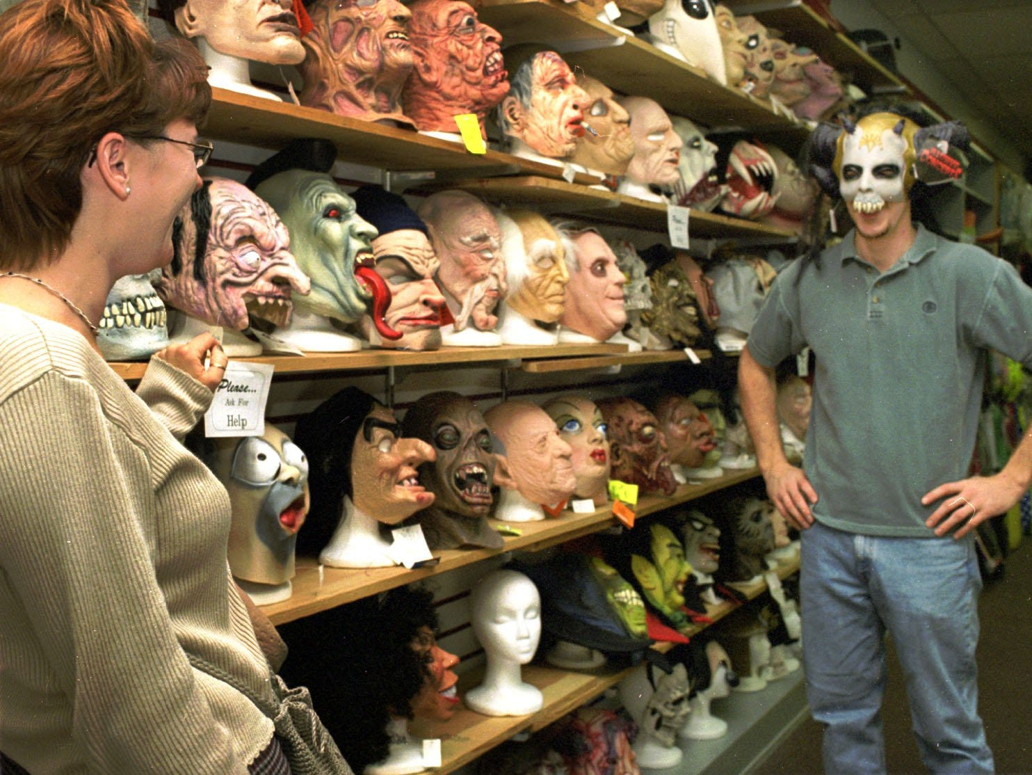1998: Dan Kithcart of Waverly tries on a Halloween mask for Lisa Plouse, also of Waverly, as they look for costumes at The Costume Place in the Arnot Mall. Counting costumes, candy and decorations, Halloween sales rank second behind Christmas, according to industry experts.