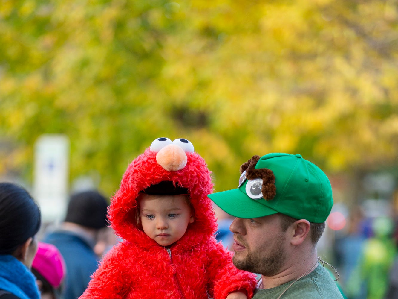 2015: Andrew Minnick holds his daughter Ariyah, who is almost, 2, Friday afternoon on N. Geneva Street as they wait for the annual Greater Ithaca Activities Center parade to make its way to The Commons for trick or treating Friday.