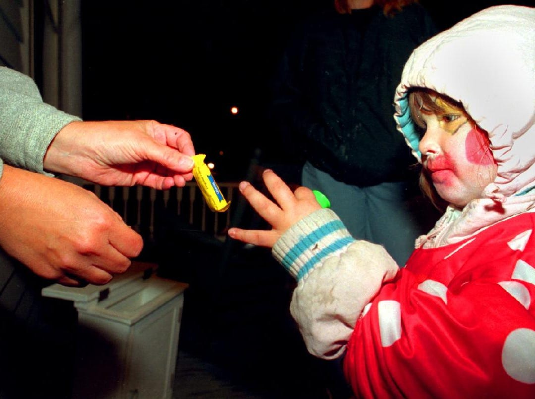 1996: Three year old Brittany Dalaba is in her clown costume as she receives some candy during her trick or treat in the west side of Binghamton, Thursday October 31, 1996. Brittany is from Binghamton.