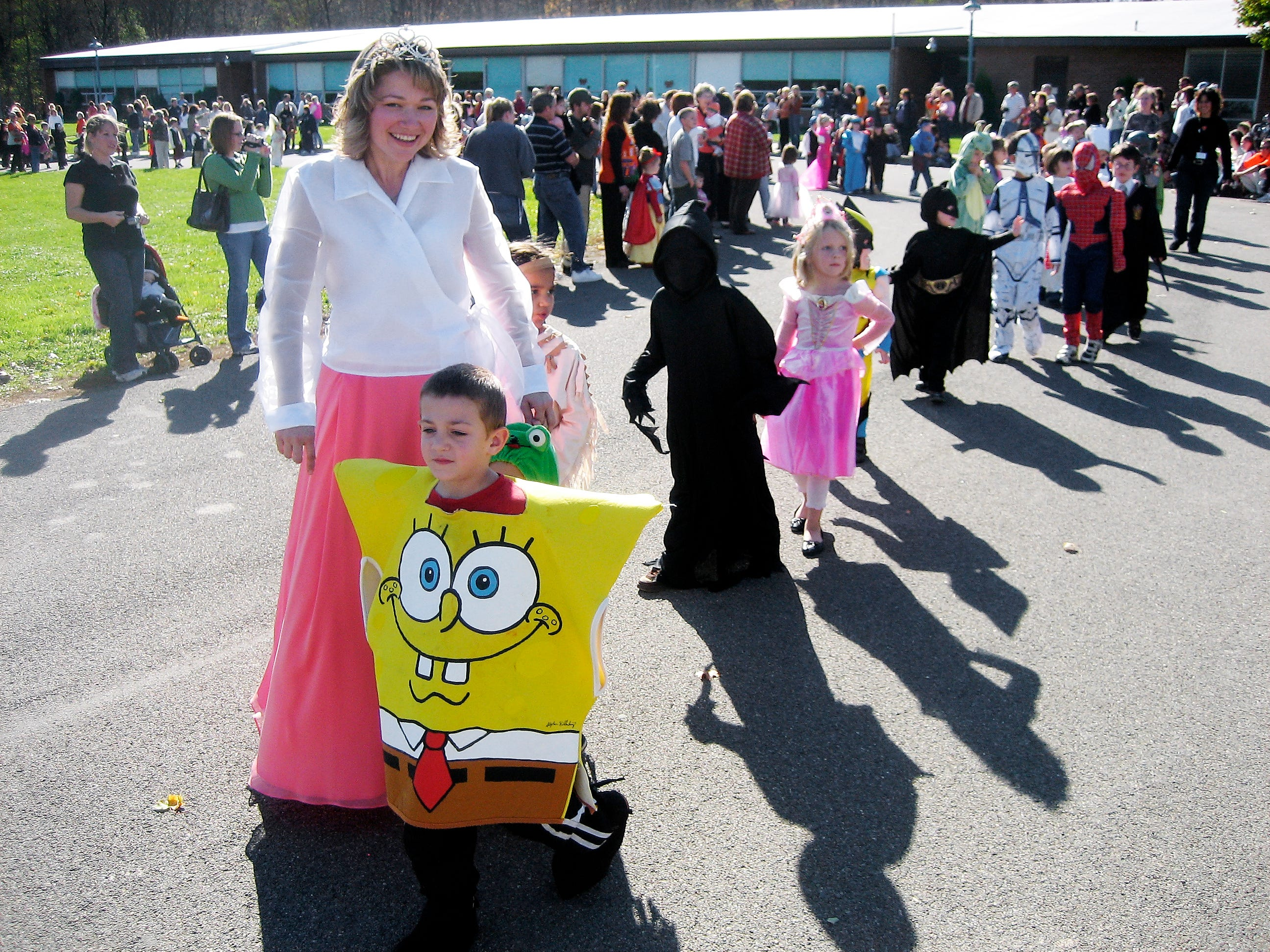 Donna Parkison, a kindergarten teacher at Brookside Elementary School, and Marcus Fiske, a kindergarten student dressed as Sponge Bob; march in the school's Halloween parade Wednesday.