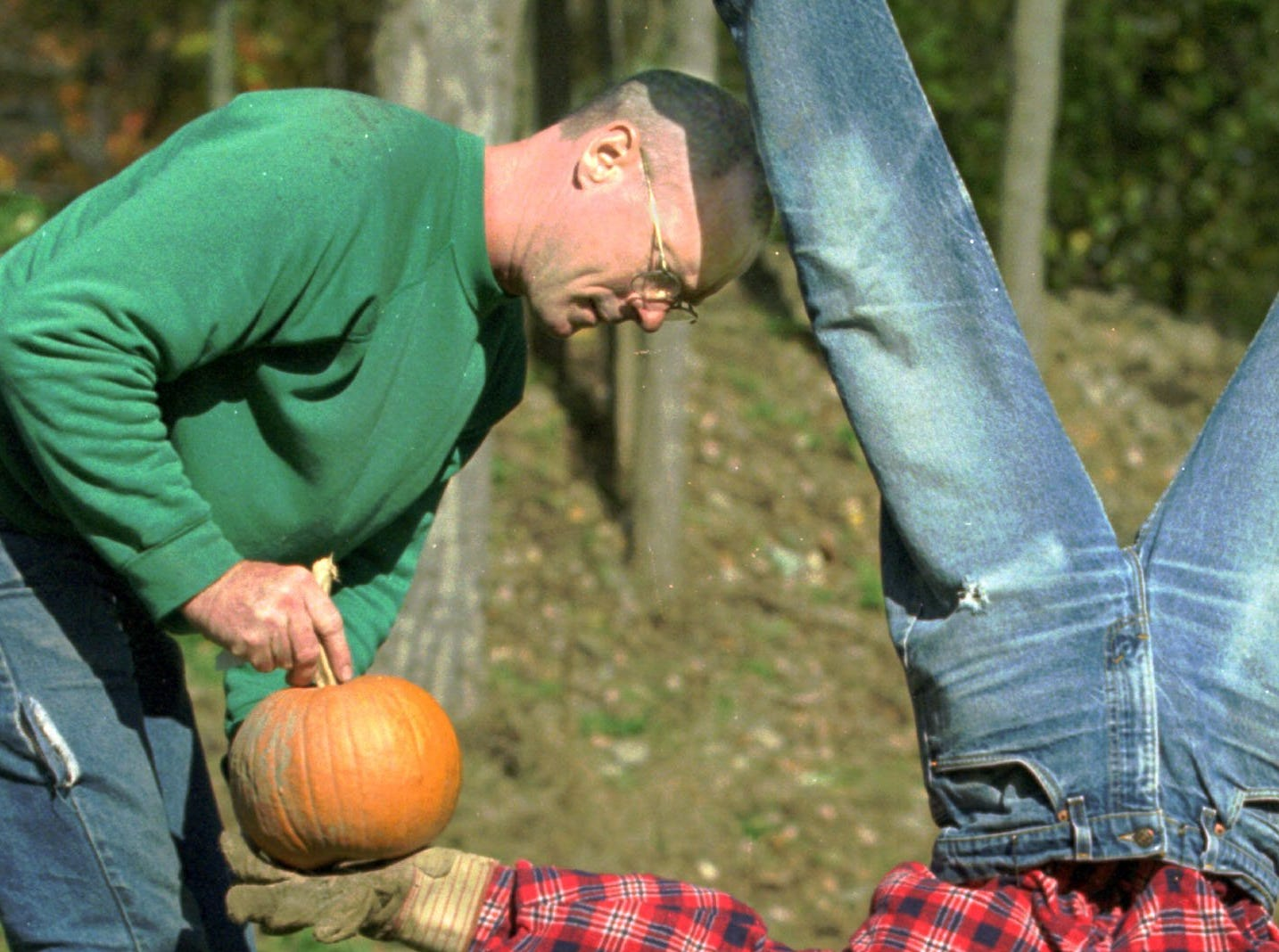 1998: Joe Ladoue, right, rearranges the pumpkin placed in the hand of his attention-getting scarecrow in Big Flats. Halloween will be observed on Oct. 31.
