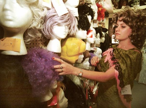 1998: Wearing a Mae West costume and wig, Daizy Noel of Johnson City looks over the wigs at Showtimes Costumes on Main Street. Noel, who is also an employee of Showtimes Costumes, plans on attending the Rocky Horror Picture Show to celebrate Halloween.