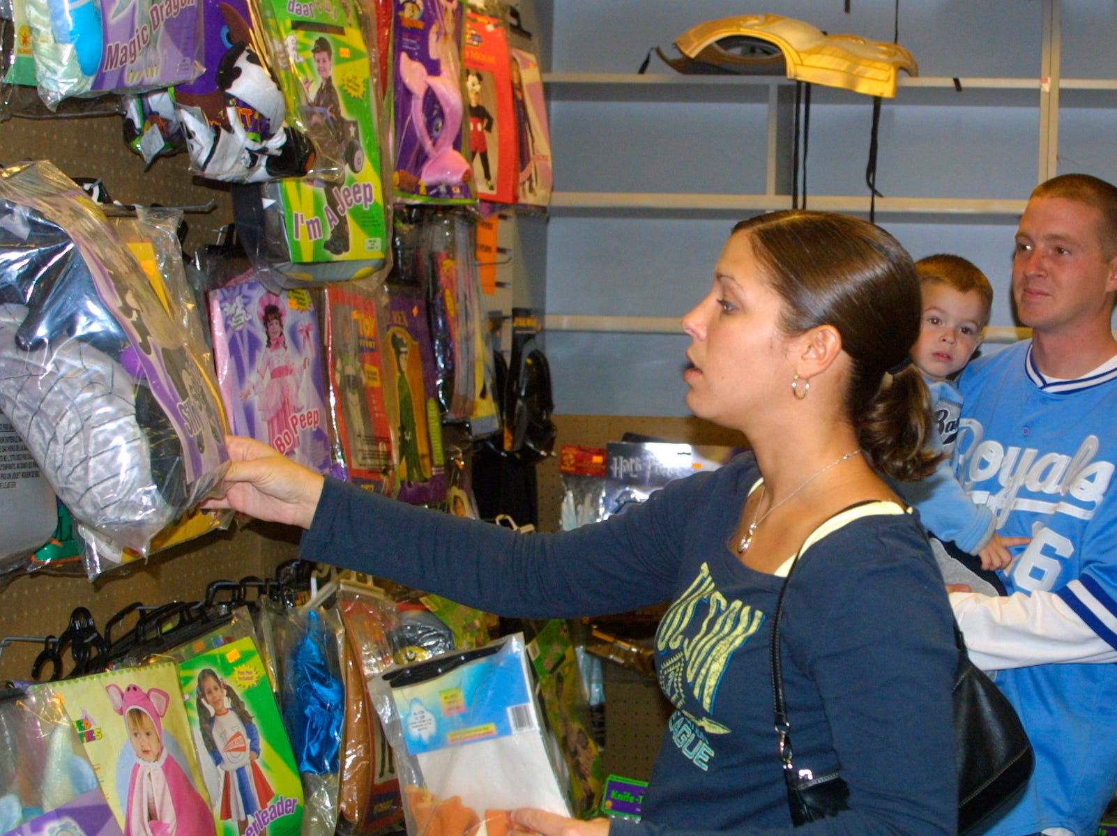 2005: Shannon Hardy, foreground, searches for a Halloween costume for he 2-year-old son, Maximus Maynard, who is being held by his father, Joe Maynard.