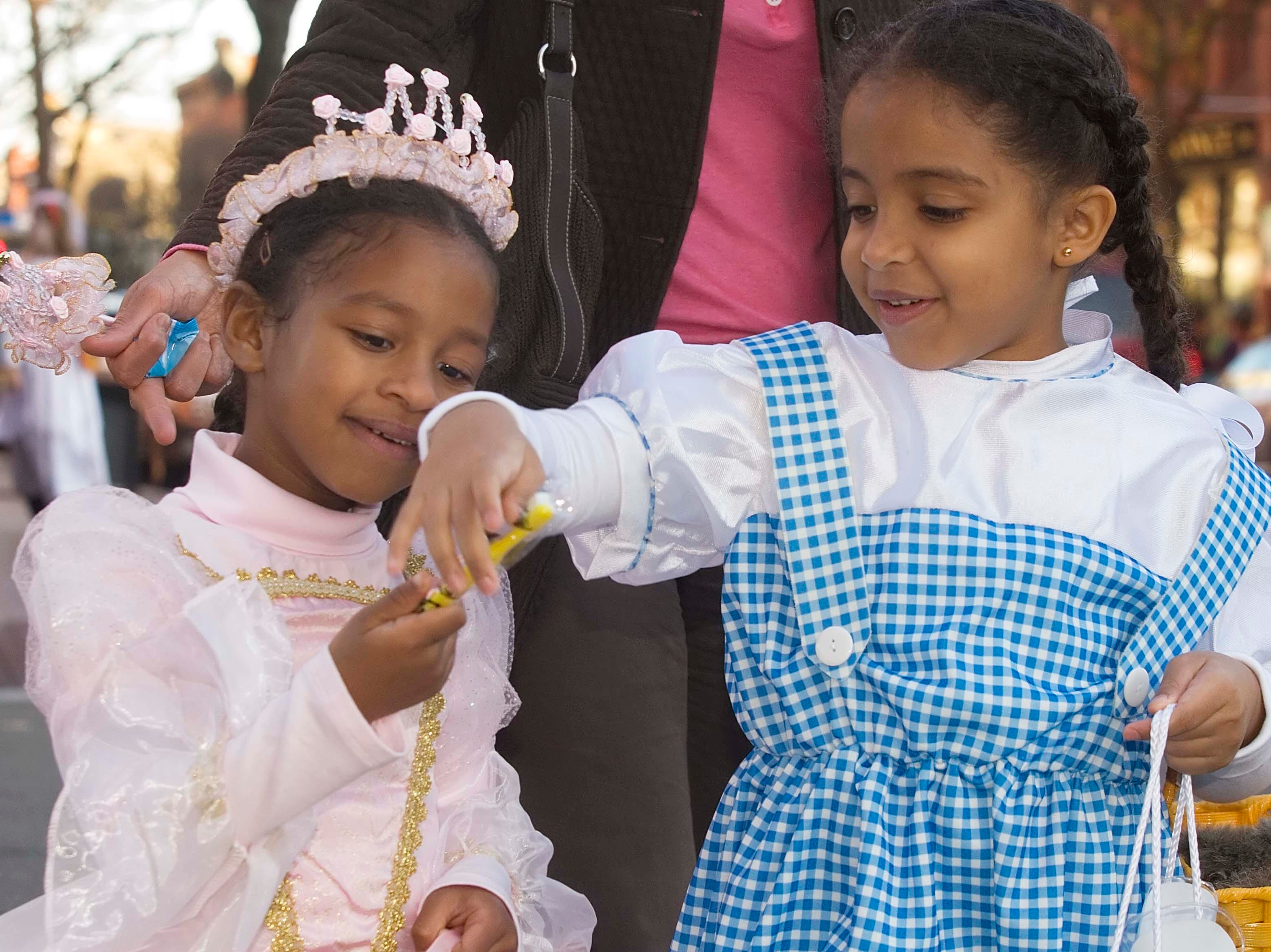 2008: Gabrielle Montgomery-Green, 5, of Big Flats left, and Raevin Shirley, 5, of Corning look at a toothbrush they Friday during trick-or-treating on Market Street in Corning.