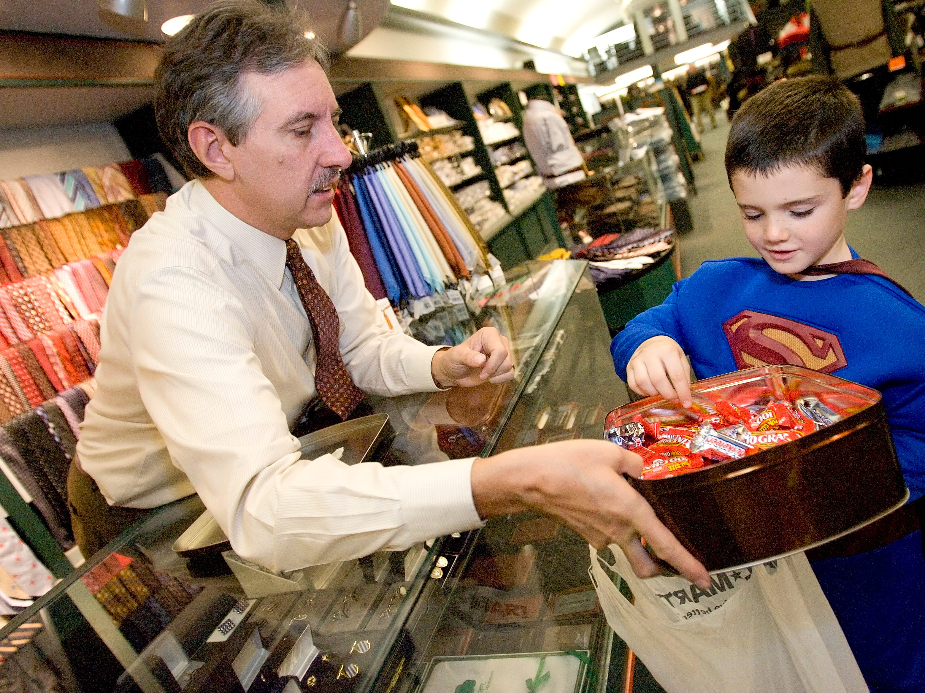 2008: Mike Jacobs, left, hands candy to Mark Hine, dressed as Superman, on Halloween afternoon at the Benjamin Peters store on The Commons. Participating merchants on The Commons welcomed trick-or-treaters from noon until 8 p.m.