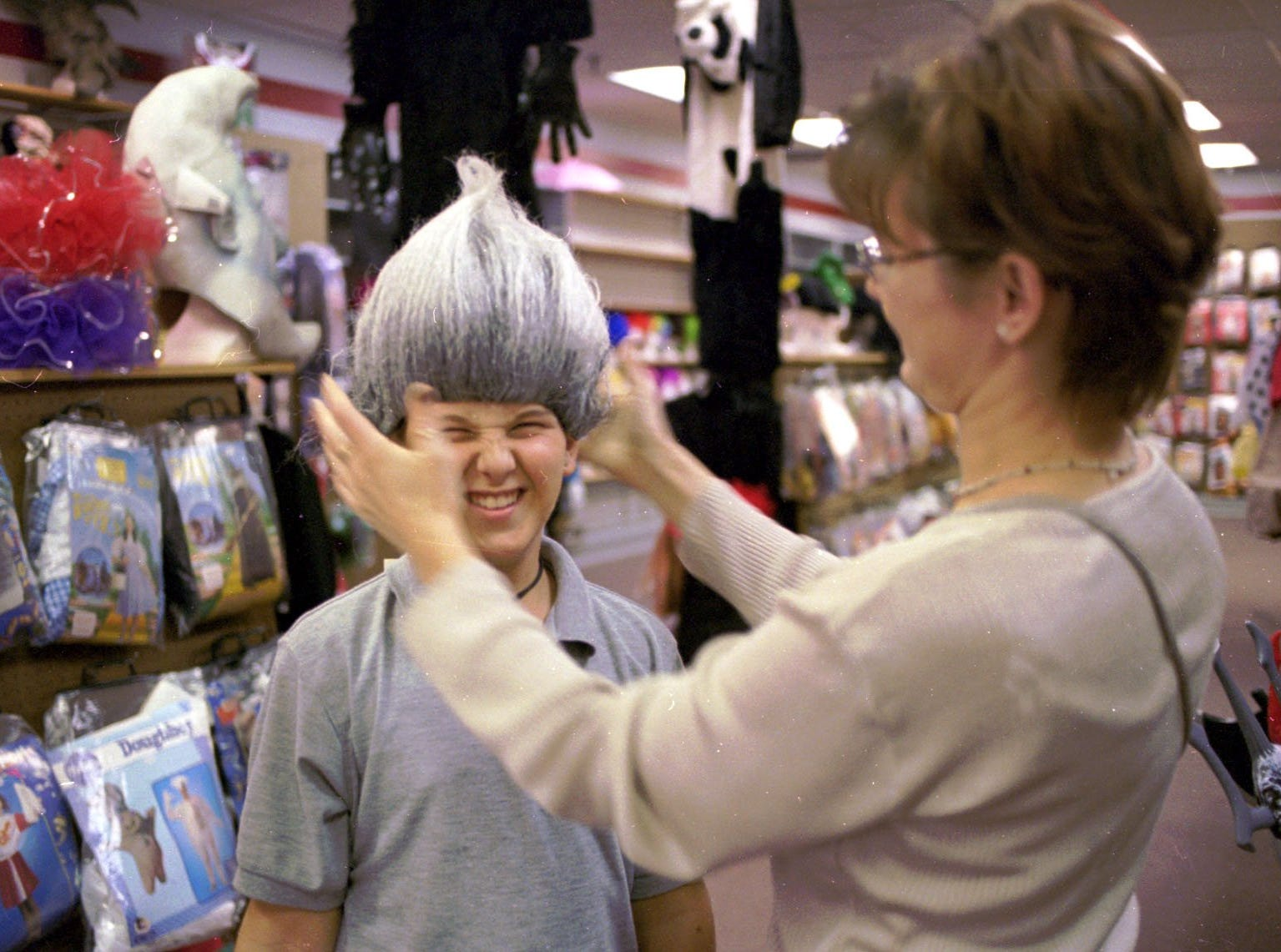 1998: Casey Dibble, 9, scrunches up his face as his mom, Lisa Plouse of Waverly, fits a Don King-type wig on him at The Costume Place at the Arnot Mall.