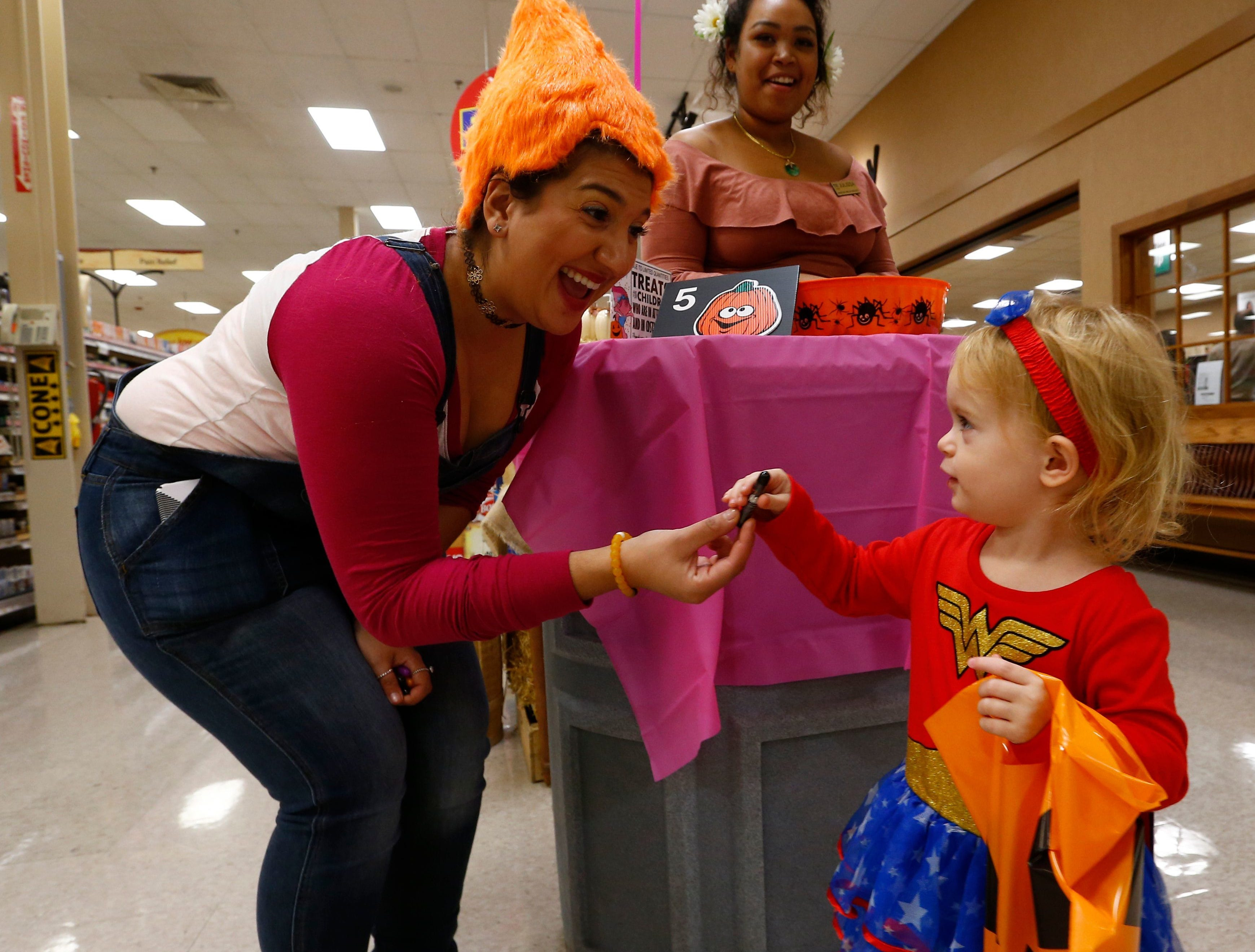 2017: Emma Koger-Hartmann gets a treat from Eva Francavilla and Julissa Thongpane during Wegmans' Halloween Parade in Johnson City on Tuesday October 24, 2017.
