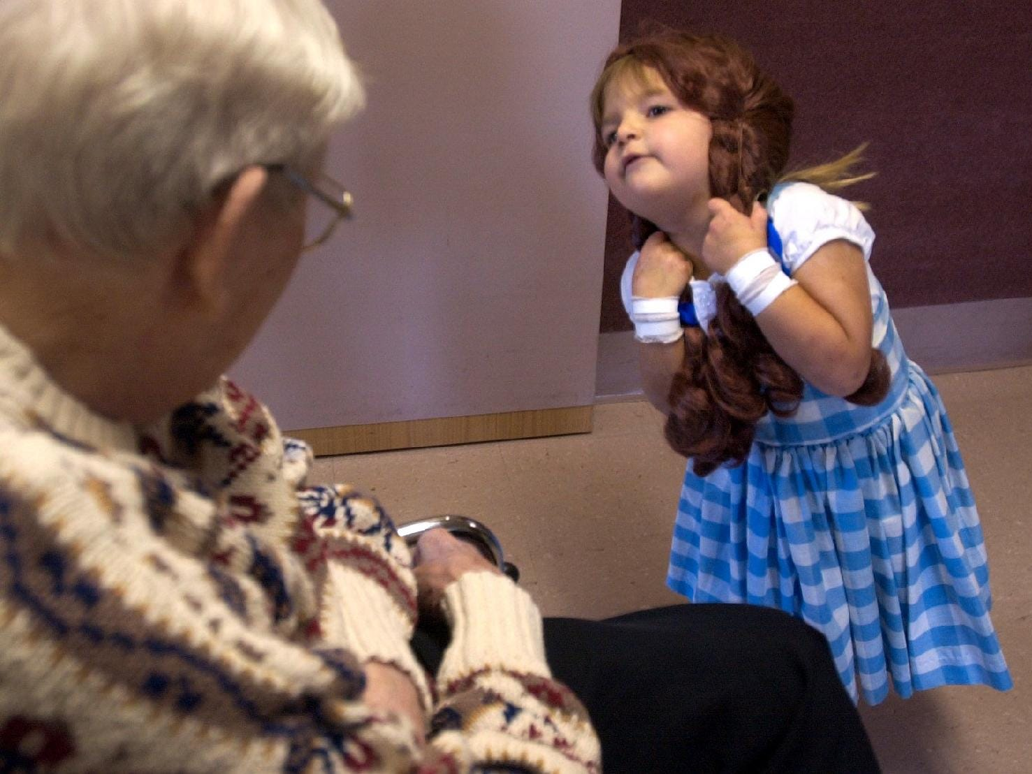 Sara Watson, 3 of Binghamton plays with the wig from her Dorothy costume during the Halloween Parade at susquehanna Nursing Home in Johnson City. About 15 children from the group Mothers and More took part in the parade.