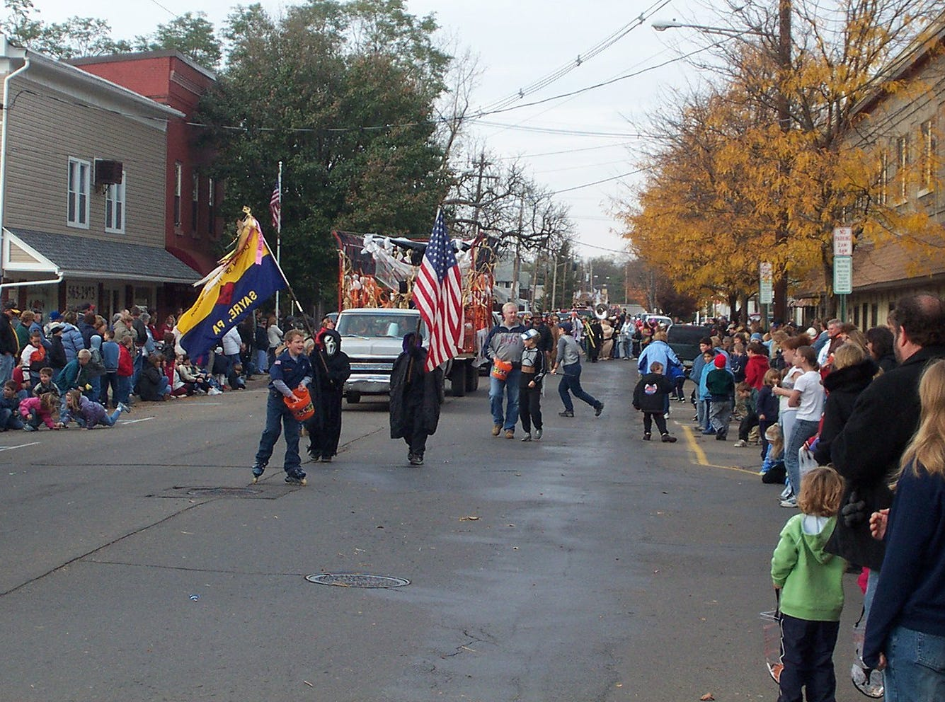2003: Marchers toss candy to the large crowd gathered for last Saturday's 47th annual Valley Halloween Parade in Waverly. All three Valley high school marching bands participated, as well as many community groups and organizations, including, at left, a group from Epiphany School in Sayre.
