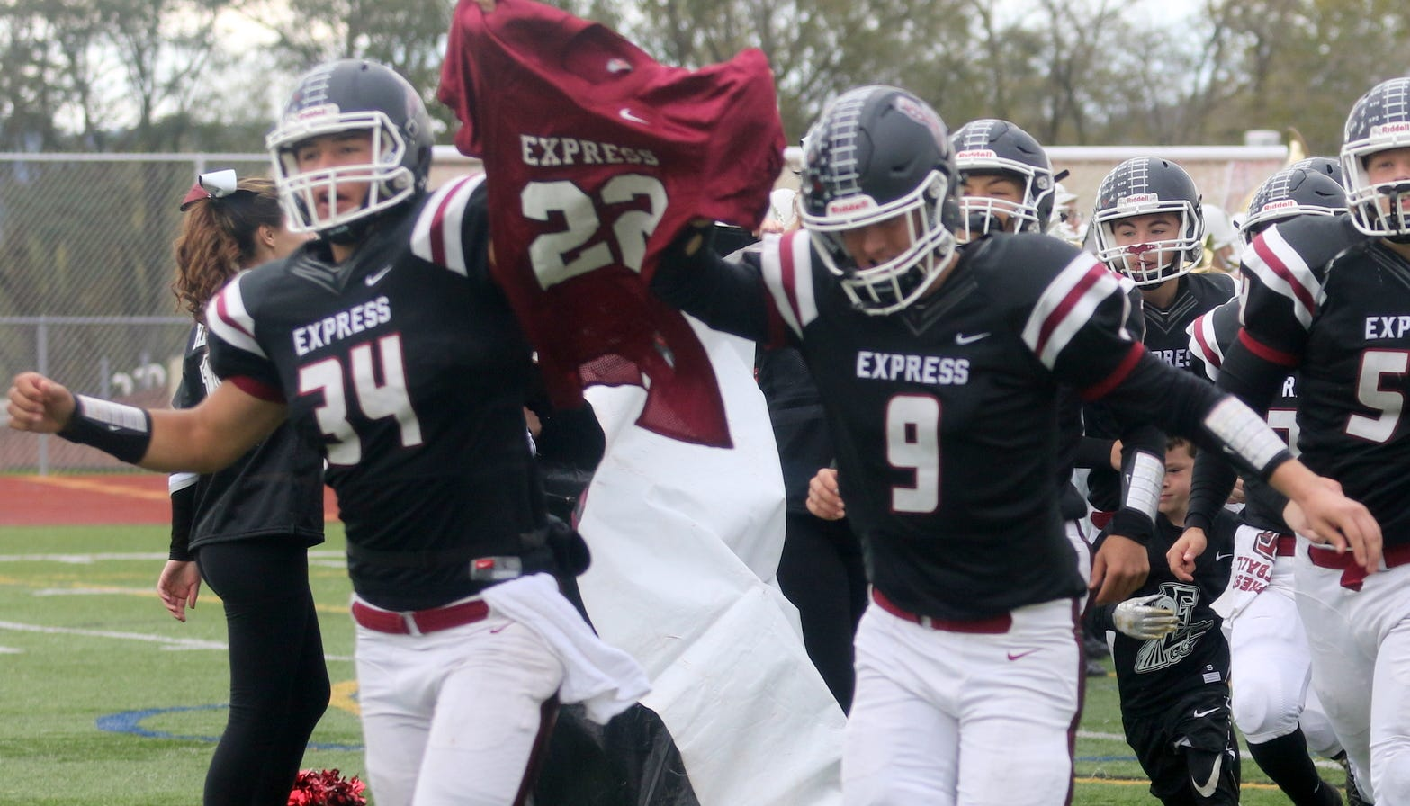 Elmira seniors Devin Hoskins (34) and Zack Middaugh (9) lead the team onto the field while carrying the jersey of former Express all-state player Eli Thomas on Oct. 20, 2018 against Vestal at Ernie Davis Academy. Thomas, who now plays at UConn, suffered a stroke Oct. 10.