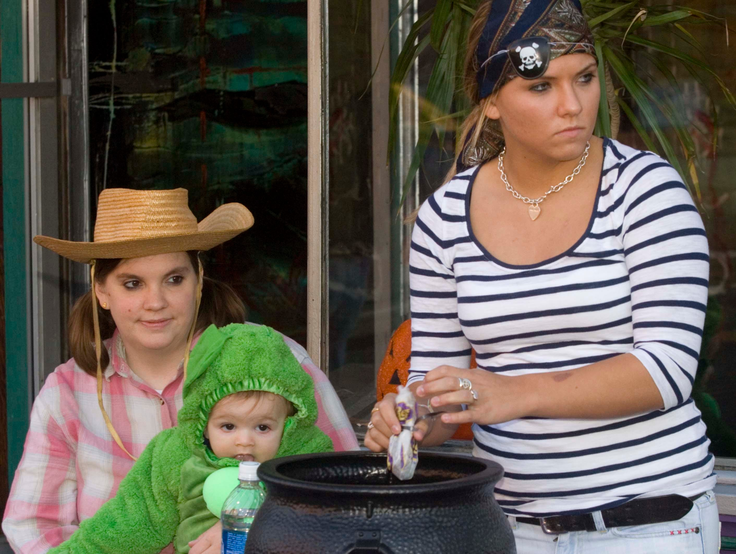 2008: Jennifer Allen, with son Jack, 6 months, both of Caton watch as Amanda Strong, 16, of Horseheads, pulls candy out of a cauldron in front of Rico's Pizza during trick-or-treating on Market Street in Corning.