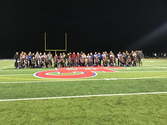 Owego Free Academy's varsity football seniors pose alongside their loved ones during senior night on Oct. 19.