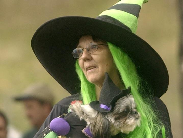 2004: Dressed as a pair of witches, Norma Letterman of Castle Creek and Abby, an 11-month old shihtzu, watch a police dog demonstration at the two-mile walk/run to benefit the Animal Care Council of Endicott and Pets Are Wonderful Support Program Sunday at Otsiningo Park.