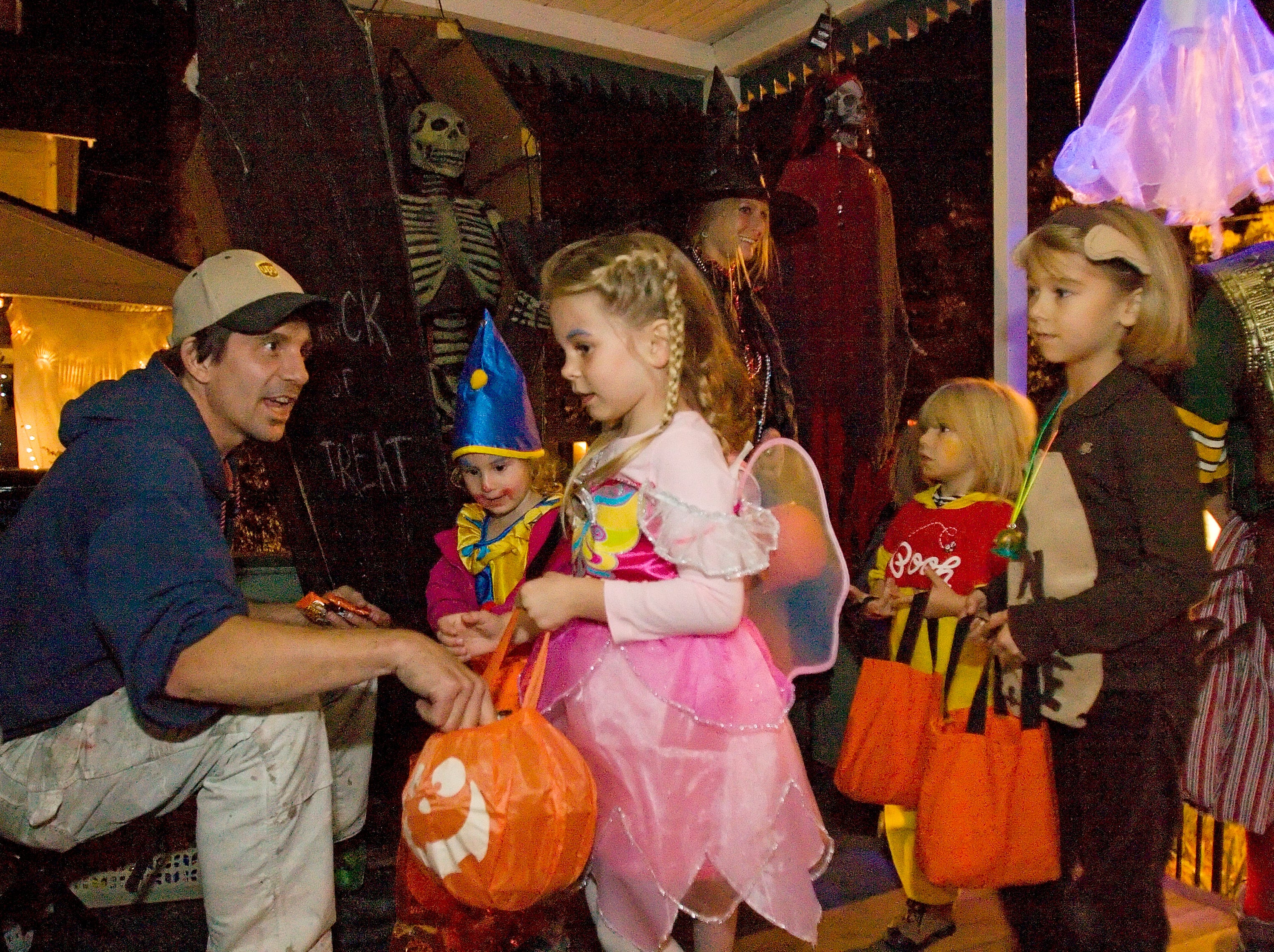 2007: Steele Steffy, left, hands out Halloween candy on his elaborately decorated front porch Wednesday night on East Falls Street in Ithaca. From left are treat-or-treaters Sabine Zentner, receiving candy from Steffy, Miriam Bakija, Greta Cotraccia, and Sophia Cotraccia.