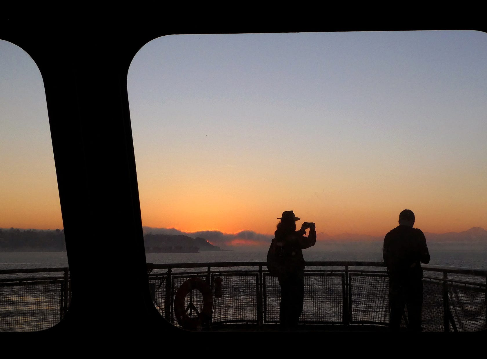The sunset breaks through fog as passengers take photos on the Seattle to Bremerton auto ferry  on Friday, October 19, 2018.