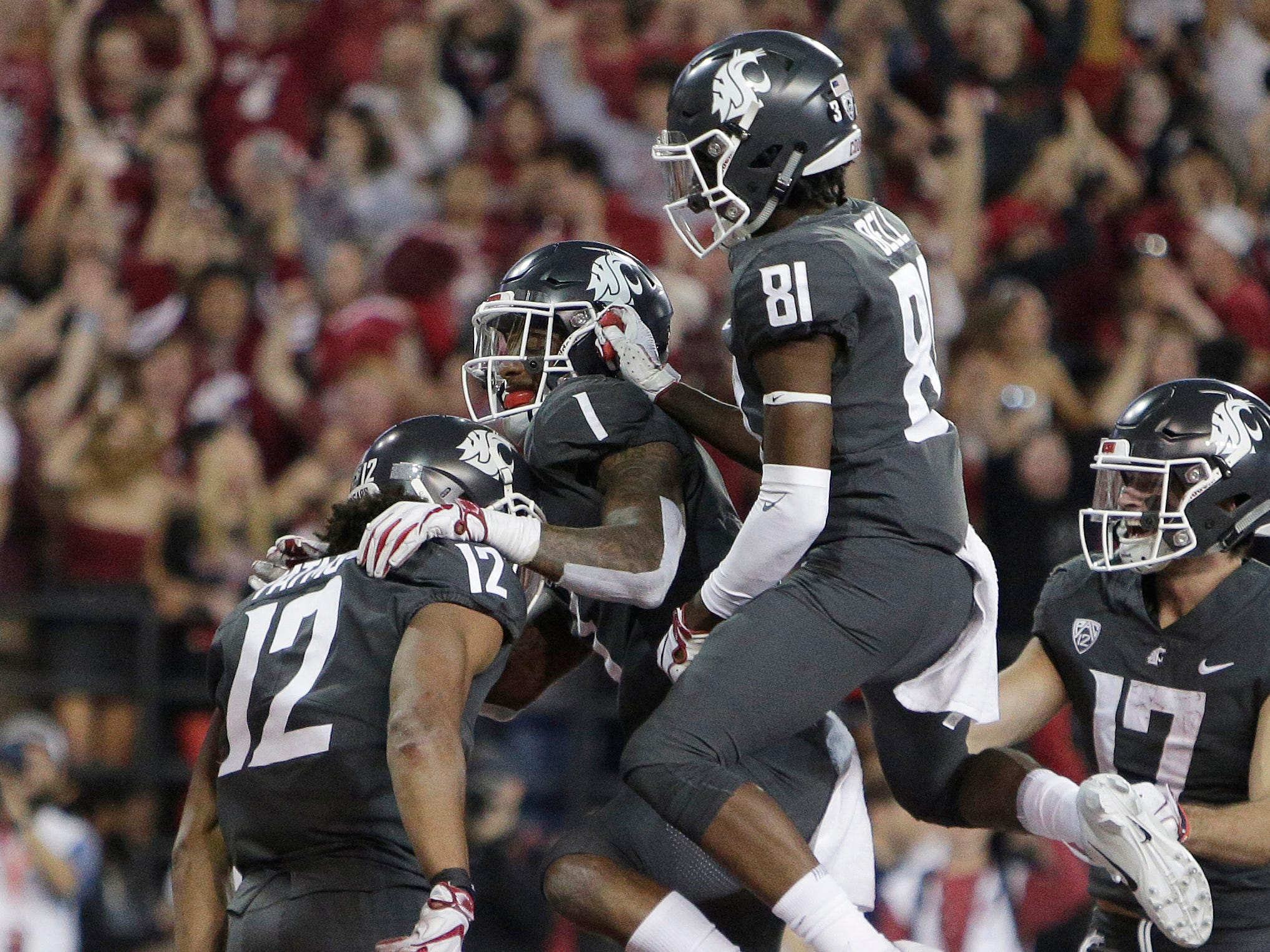 Washington State wide receiver Dezmon Patmon (12) celebrates his touchdown catch with wide receiver Davontavean Martin (1) and wide receiver Renard Bell (81) during Saturday's win over Oregon.