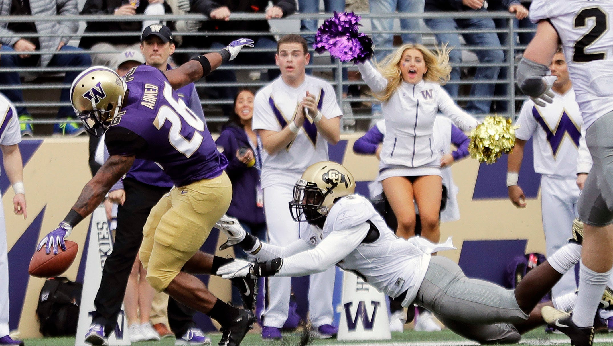 Washington running back Salvon Ahmed, left, scores a touchdown during Saturday's win over Colorado in Seattle.