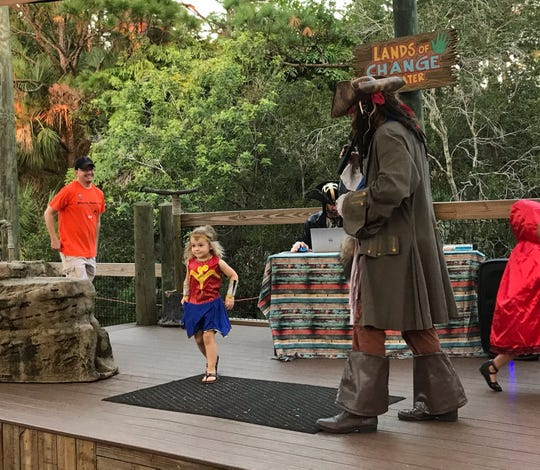 Isabella on stage at Boo at the Zoo during the costume contest. She gets set to leap off the stage after telling Jack Sparrow her name.