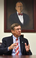 T. Dwayne McCay, president of the Florida Institute of Technology, speaks alongside a portrait of university founder Jerome Keuper.
