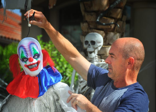 Mike and Amy Spurny go all out, taking most of the day to decorate their Fairway Lakes home in Viera for Halloween. The home is a favorite for local trick-or -treaters. Mike Spurny hangs a sounds activated clown from a tree near the sidewalk that catches people of guard.