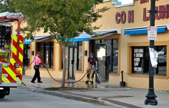 Jacksonville Fire and Rescue personnel use chemicals and hoses to clean the blood outside the Maytag Coin Laundry on A Philip Randolph Boulevard, Sunday, Oct. 21, 2018, in Jacksonville, Fla., after a street shooting earlier in the day, several blocks away from TIAA Bank Field where the Jacksonville Jaguars and Houston Texans played an NFL football game. (Bob Self/The Florida Times-Union via AP)