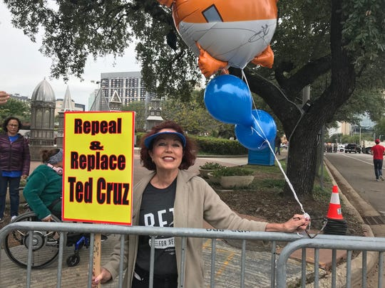 """Gretchen Lindquist of Houston has a message for Sen. Ted Cruz — """"he's done nothing for Texas but shut down the government and read Green Eggs and Ham."""" She held a sign and wore a Tshirt for his opponent -Democrat Beto O'Rourke - as she stood outside the Toyota Center on Monday, Oct. 22, 2018."""