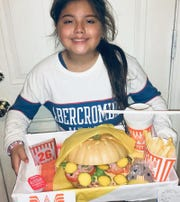 Madison Rodriguez, 11, holds her Whataburger-inspired pumpkin she decorated for a contest at her elementary school in El Paso, Texas.