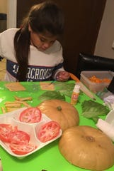 Madison Rodriguez, 11, paints Mod Podge on a slice of cheese to make her Whataburger-inspired pumpkin.