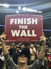 Holly Crane on the floor of Houston's Toyota Center tells those in the bleachers why she attended the rally headlined by President Donald Trump.