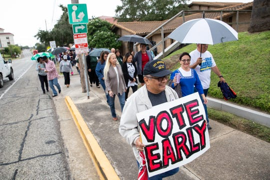 People march down North Tancahua Street to the Nueces County Courthouse to voter as they take part in Indivisible's March The Vote on the first day of early voting in Texas on Monday, Oct. 22, 2018.