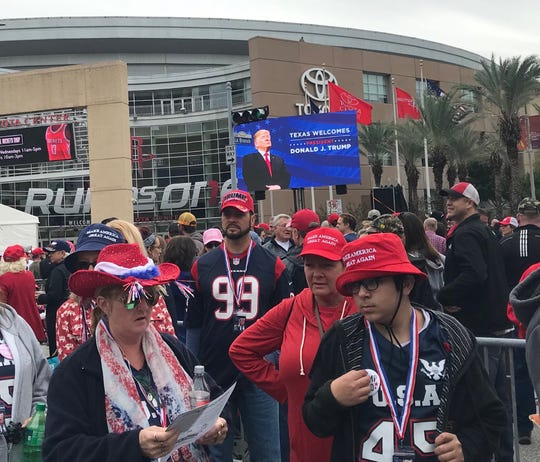 The crowd outside the Toyota Center listens to music under the image of President Donald Trump on a giant monitor ahead of his rally on Monday, Oct. 22, 2018.