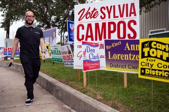 A voter walks past a line of campaign signs outside the Deaf and Hard of Hearing Center of Corpus Christi on the first day of early voting on Monday, October 22, 2018. Some voters said the wait times ranged from 30 minutes to an hour.