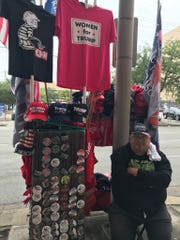 """Steve Scanlon of Connecticut sells President Donald Trump-related hats, shirts and buttons at his 109th rally since 2016 outside the Toyota Center in Houston on Monday, Oct. 22, 2018. He says he makes """"a bit of a living"""" but mostly does it because he believes in Trump."""