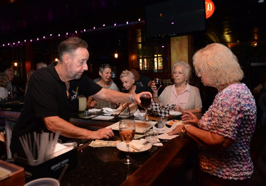 Former Coastline bartender Mitch Brodsky serves a glass of wine to a patron during Golden Oldies night at Vera's Bar and Grill in Cherry Hill, Monday, Sept. 10, 2018.