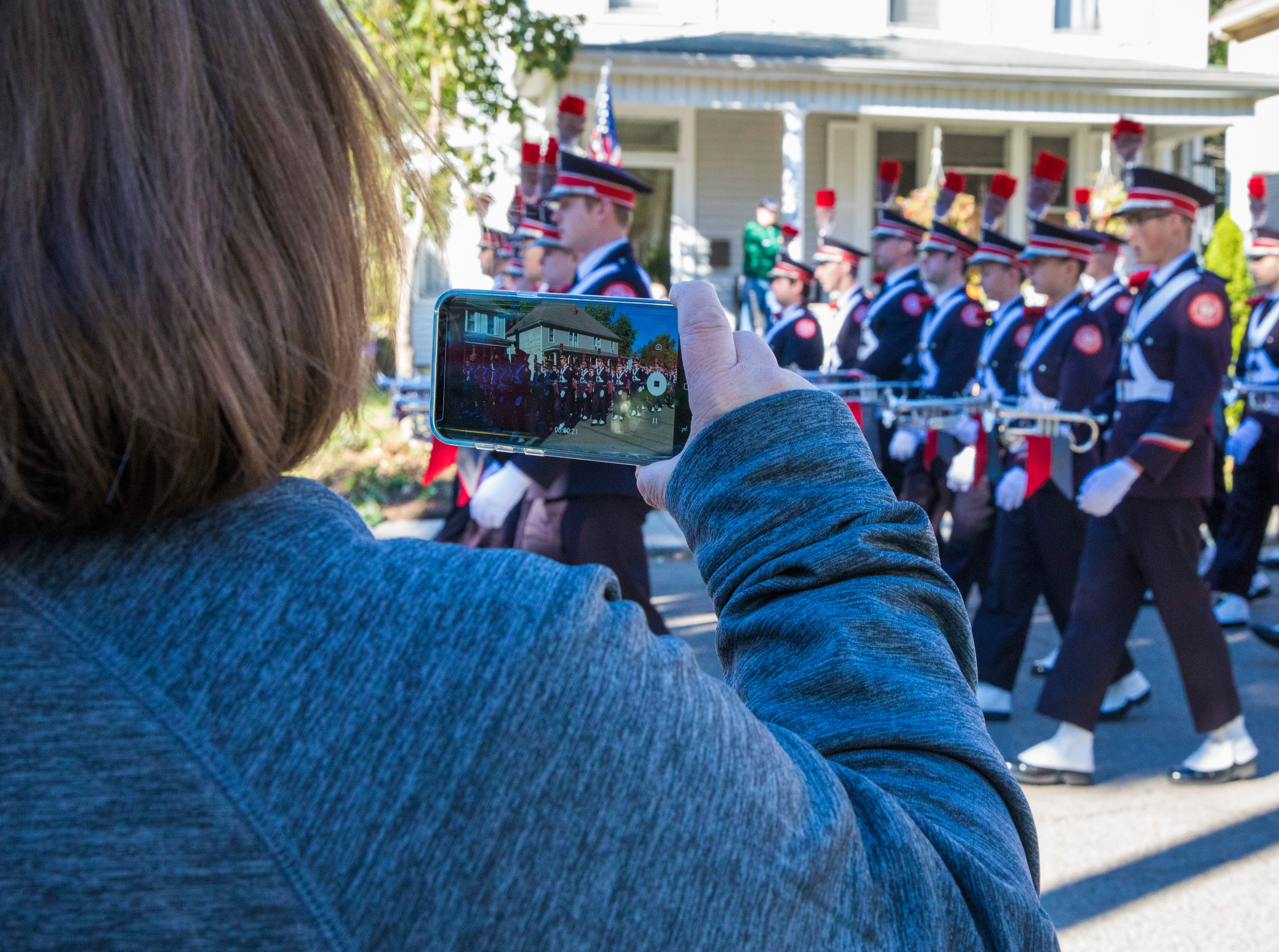 A local resident stands on the sidewalk and watches THE Ohio State Band perform down Arch Street and takes video before their performance at Chillicothe's Herrnstein field on Sunday, October 21, 2018.