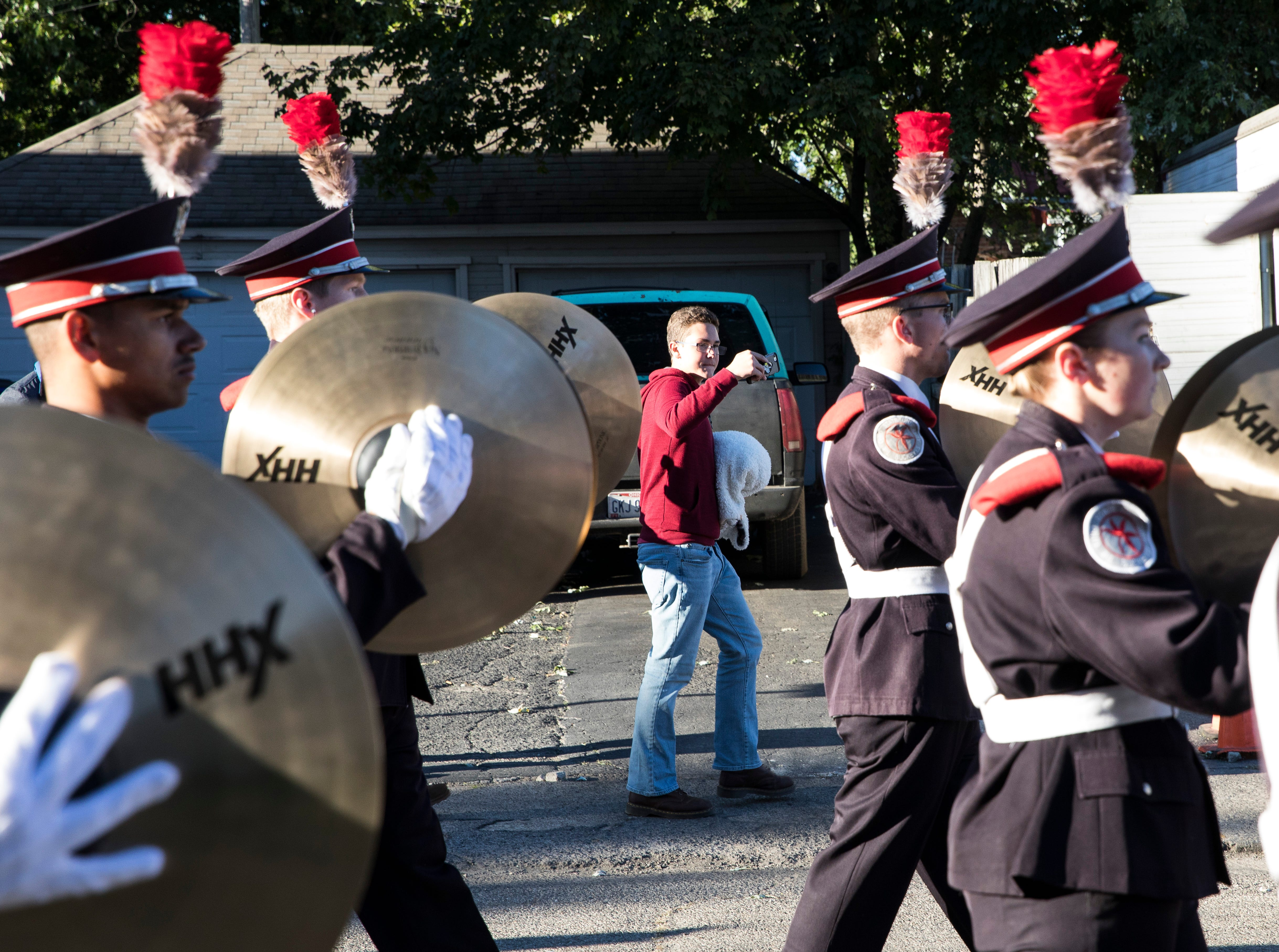 Chillicothe student Trace Yocum walks alongside THE Ohio State Band and takes video as they perform down Arch street after their performance at Chillicothe's Herrnstein field on Sunday, October 21, 2018.