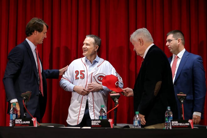 From left: Cincinnati Reds President of Baseball Operations Dick Williams, new field manager David Bell, Reds CEO Bob Castellini, General Manager Nick Krall, all smile as Bell puts on a No. 25 uniform during his introduction as the next field manager, Monday, Oct. 22, 2018, at Great American Ball Park in Cincinnati.