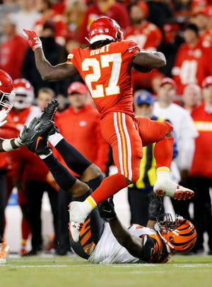 Kansas City Chiefs running back Kareem Hunt (27) leaps over Cincinnati Bengals linebacker Vontaze Burfict (55) after stiff arming him to the ground on a carry in the third quarter of the NFL Week 7 game between the Kansas City Chiefs and the Cincinnati Bengals at Arrowhead Stadium in Kansas City, Mo., on Tuesday, Oct. 16, 2018. The Bengals lost 45-10, falling to 4-3 on the season.