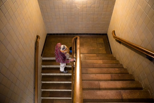 A construction worker paints the railing in the stairs at The Madcap Education Center on Monday, Oct. 22, 2018 in Cincinnati.